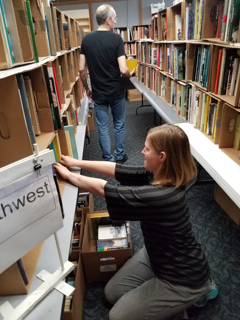 "That's Membership Coordinator Jessica Galuska hard at work organizing books in the ""Northwest"" section of the sale. (Pat Harper photo)"